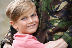 Sohn, der Militärvater Home On Leave umarmt lizenzfreies stockfoto