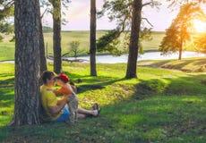 Sohn, der seinen Vater umarmt und küsst Familienurlaub im Kiefernwald auf dem Ufer des Sees Stockbild