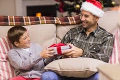 Sohn, der Vater ein Weihnachtsgeschenk auf der Couch gibt Lizenzfreies Stockfoto