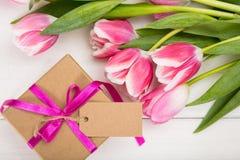Sohn gibt der Mama eine Blume Rosa Tulpen und ein Geschenk der leeren Karte auf weißem Hintergrund, Draufsicht, Kopienraum lizenzfreie stockfotos