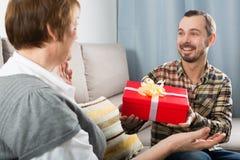 Sohn gibt der Mutter Geschenk lizenzfreie stockfotos