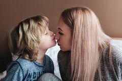 Sohn küsst seine Mutter Mamma und Sohn Glücklicher Mutter`s Tag Mutter, die zu Hause ihr Kind umarmt lizenzfreie stockfotos
