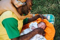 Sohn lehnt sich auf Schulter des Lügenvatis, der sein neugeborenes Kind betrachtet lizenzfreies stockfoto