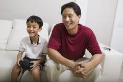 Sohn-Spiel-Videospiel des Vaters überwachendes auf Couch Lizenzfreies Stockbild