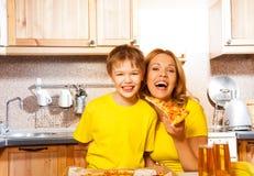 Sohn und lachende Mutter, die Scheibe der Pizza halten lizenzfreies stockfoto