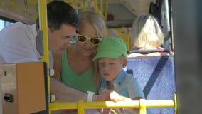 Sohn und Mutter, die Vatis smartwatch im Bus verwendet stock video footage
