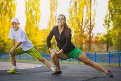 Sohn und Mutter tun Übungen auf dem Stadion Lizenzfreie Stockbilder