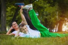 Sohn und Mutter tun Übungen im Park Lizenzfreie Stockfotos