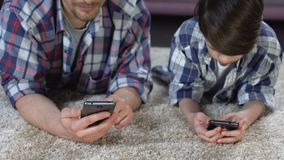 Sohn und sein Vater, die sich auf dem Boden spielt auf Smartphones, Mangel an Sorgfalt hinlegt stock video