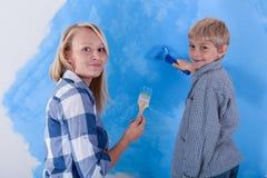 Sohn und seine junge Mutter, welche die neue Wohnung malen Lizenzfreie Stockfotografie