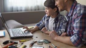 Sohn und Vater, die bei Tisch, PC-Videotutorium zusammen suchend auf Laptop sitzt stock video footage