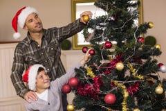 Sohn und Vati, die den Weihnachtsbaum verzieren Stockbilder