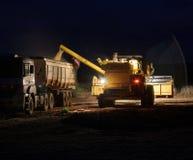 Soia di versamento del trattore sul camion alla notte Immagine Stock