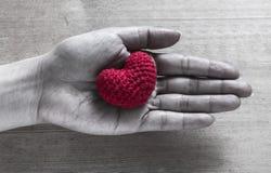 Soie en forme de coeur rouge sur des mains Photo libre de droits