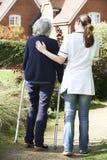Soignant aidant la femme supérieure à marcher dans le jardin utilisant le cadre de marche Photographie stock libre de droits