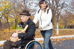 Soignant de sourire poussant un vieil homme dans un fauteuil roulant Photo stock