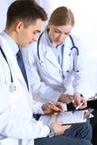 Soigne des papiers à lettres utilisant le presse-papiers Médecins discutant le programme de médicament ou étudiant à la conférenc photo stock
