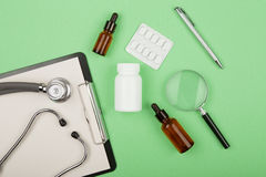 soigne le lieu de travail - comprimé médicinal, stéthoscope, pilules et loupe photographie stock libre de droits