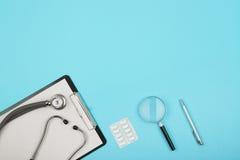 soigne le lieu de travail - comprimé médicinal, stéthoscope, pilules et loupe image stock