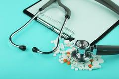 soigne le lieu de travail - comprimé médicinal, stéthoscope, pilules et loupe Photo stock
