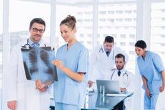 Soigne le rayon X de examen avec des collègues à l'aide de l'ordinateur portable derrière image libre de droits