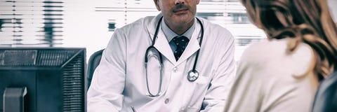 Soignez écouter son patient parlant de sa maladie photographie stock libre de droits