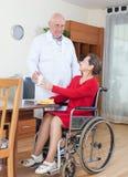 Soignez amener la femme handicapée à la table de dîner Images libres de droits