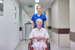 Soignez avec la femme supérieure dans le fauteuil roulant à l'hôpital Photo stock