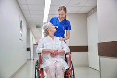 Soignez avec la femme supérieure dans le fauteuil roulant à l'hôpital Photos libres de droits