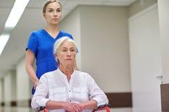 Soignez avec la femme supérieure dans le fauteuil roulant à l'hôpital Photo libre de droits