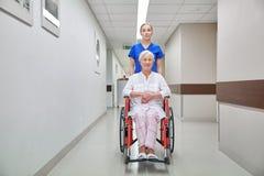 Soignez avec la femme supérieure dans le fauteuil roulant à l'hôpital Image libre de droits