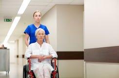 Soignez avec la femme supérieure dans le fauteuil roulant à l'hôpital Photographie stock libre de droits