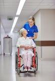 Soignez avec la femme supérieure dans le fauteuil roulant à l'hôpital Images libres de droits