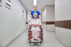 Soignez avec la femme supérieure dans le fauteuil roulant à l'hôpital Image stock
