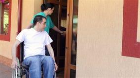Soignez avec le jeune homme dans le fauteuil roulant faisant une promenade banque de vidéos