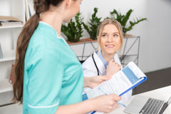 Soignez avec le stylo et le presse-papiers regardant le docteur de sourire à l'aide de l'ordinateur portable Photos stock