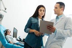 Soignez demander à la mère du petit patient de signer des documents Photographie stock