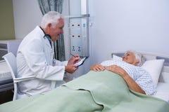 Soignez discuter le rapport avec le patient supérieur dans la salle Photographie stock libre de droits