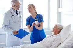Soignez donner la médecine à la femme supérieure à l'hôpital Photographie stock