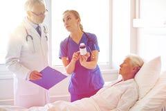 Soignez donner la médecine à la femme supérieure à l'hôpital Photos stock