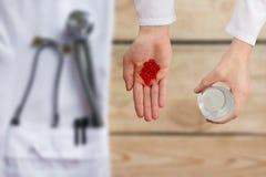 Soignez donner les pilules rouges et le verre de l'eau, mains se ferment avec le bureau sur le fond, vue supérieure Image stock