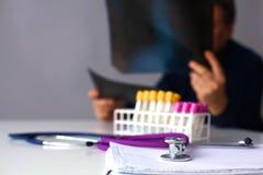 Soignez examiner un rayon X à une table dans son bureau photo stock