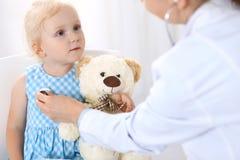Soignez examiner une petite fille blonde avec le stéthoscope Concept de médecine et de soins de santé image libre de droits