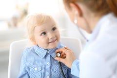 Soignez examiner une petite fille blonde avec le stéthoscope Concept de médecine et de soins de santé photo stock