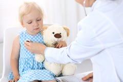 Soignez examiner une petite fille blonde avec le stéthoscope Concept de médecine et de soins de santé images libres de droits