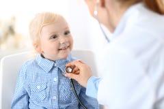 Soignez examiner une petite fille blonde avec le stéthoscope Concept de médecine et de soins de santé photographie stock libre de droits