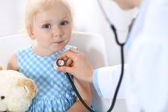 Soignez examiner une petite fille blonde avec le stéthoscope Concept de médecine et de soins de santé photos stock