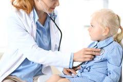 Soignez examiner une petite fille blonde avec le stéthoscope Concept de médecine et de soins de santé images stock