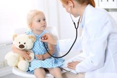 Soignez examiner une petite fille blonde avec le stéthoscope Concept de médecine et de soins de santé photographie stock