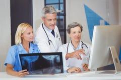 Soignez l'équipe avec le rayon X tout en discutant au bureau d'ordinateur Photo stock